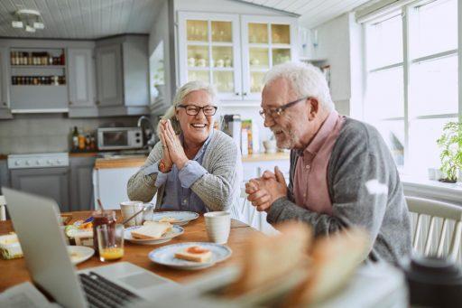 ouderen aan tafel met ontbijt en laptop